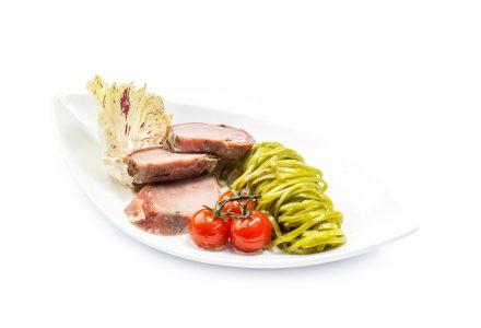 Schweinefilet am Stück gebraten in Serrano-Mantel auf grünen Bandnudeln mit geschmolzenen Tomaten